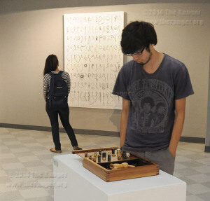 "Communication design sophomore Ronn Jackel and art sophomore Ana Burkwell view the Ray Cox ""Palimpsest"" exhibition Tuesday in visual arts. Jackel observed a piece titled ""The Cats Dreaming Together,"" a wooden checkerboard with toy cats inside and letter tiles spelling out the title. Burkwell observed ""Found Writing,"" a white board with bent metal wires hung with nails. The exhibit's opening reception is 6 p.m. to 8 p.m. Oct. 9 and runs until Dec. 5. Gallery hours are 8 a.m. to 7 p.m. Monday to Thursday and 8 a.m. to 5 p.m. Friday. The gallery is closed on the weekend and also will be closed Nov. 27-30 for Thanksgiving. Photo by Ian Coleman"