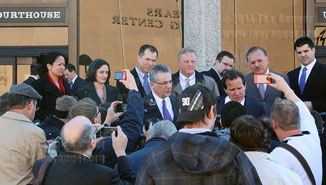 Attorney Neel Lane, bottom right, answers questions from the media Wednesday outside the John H. Wood Jr. U.S. Courthouse. The plaintiffs Cleopatra De Leon, Nicole Dimetman, Vic Holmes and Mark Phariss are together in the top center after the court adjourned. Photo by M.J. Callahan