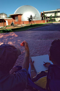 Architecture professor Joaquin Escamilla explains proportion to architecture freshman Jesse Gutierrez Tuesday west of Nail Technical Center. Escamilla's freehand drawing class was sketching Scobee Planetarium.