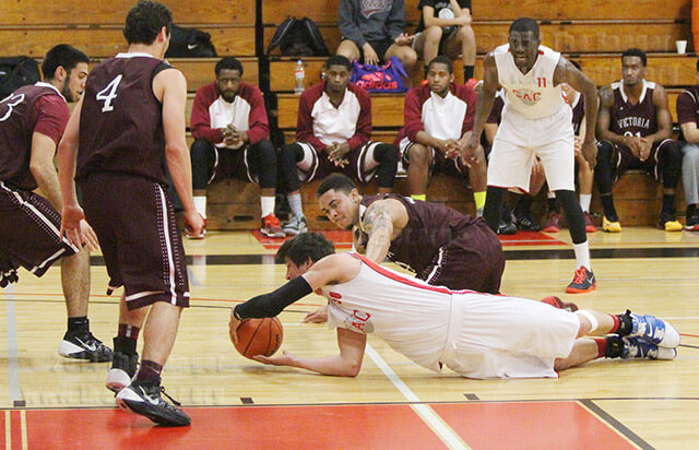 Kinesiology sophomore Chris Huber and Pirates guard Shannon Winston scramble for a loose ball. Photo by Catharine Treviño