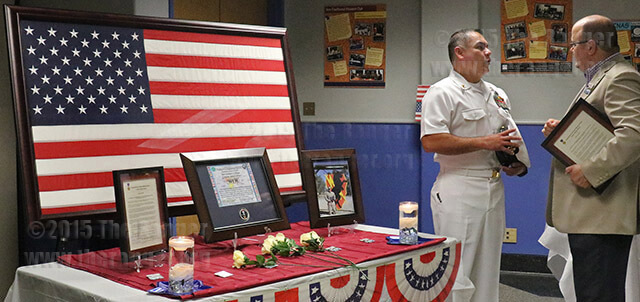Sixty attended the Memorial Day ceremony Monday in Loftin. Luis Arellano, retired chief petty officer, speaks with President Robert Vela about the donated American Flag that was flown over Kabul, Afghanistan, during Operation Enduring Freedom on Sept. 1, 2012. The flag, which was donated by the headquarters of the International Security Assistance Force, will be displayed in the veteran's affairs office. Photo by Alyssa Zapata