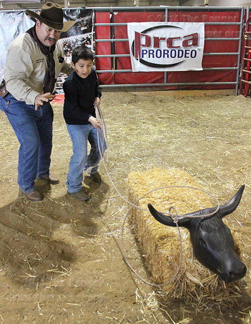 Roper Joseph Piccolella guides Roy Medrano, 8, in his first roping experience in the Rodeo Discovery area of the Expo Hall Saturday. Rodeo Discovery, in its first year, is made available to children to teach them to rope using a safe hay-dummy alternative to an actual cow. Photo David Guel