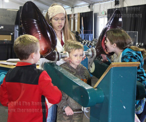 Ryan Lyssy, 8, listens while his sister, Rachael Lyssy, 13, yells into artificial bat ears meant to demonstrate amplification of bat hearing in the new Bats, Mysteries and Myths exhibit Saturday. Ryan and Rachael and their friends, Bella Dzurk, 13, and Layne Gisle, 7, traveled from Falls City with their family to watch bullriding. Photo by Mandy Derfler