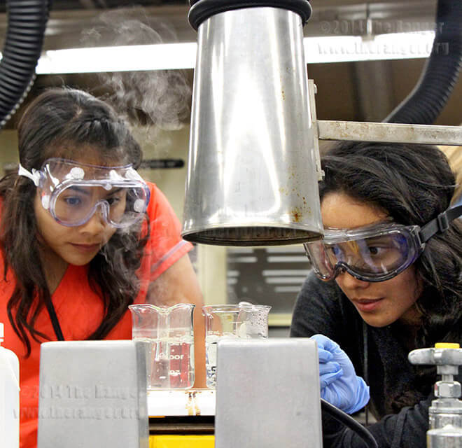 Biology sophomores Sayuri Garcia and Dolores Garcia observe 1M thiocatemide and 1M ammonium acetate while conducting a qualitative analysis experiment during CHEM 1412, General Chemistry 2, lab Wednesday in chemistry and geology. A hot plate was used to boil deionized water so they could control the temperature of the chemicals inside the test tubes. Garcia said she enjoys seeing what she learned in lecture. Both students said Chemistry 2 is an interesting class. Photo by Daniel Carde
