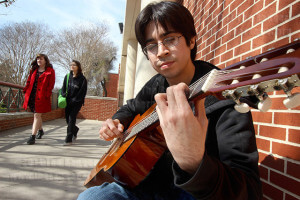 Music sophomore Giovanni Medrano is playing an original untitled composition on guitar Wednesday on the south side of Loftin. Medrano says he has been interested in guitar for about seven years and often plays between classes. Photo by Daniel Carde