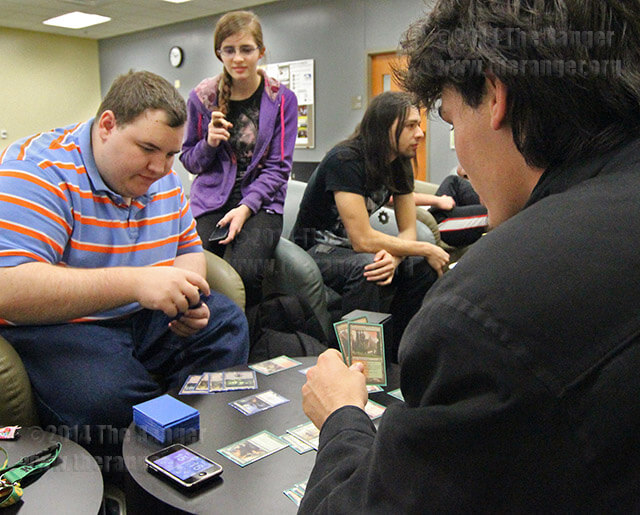 """Accounting sophomore Josh Yoder prepares to play """"Magic: The Gathering"""" against engineering sophomore John Boehm Tuesday in commons at Northeast Lakeview. Yoder, with 14 years of playing this card game, outwitted Boehm for a second straight win, using a cell phone to keep track of life levels. Photo by Daniel Carde"""