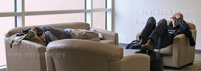 """Kinesiology sophomore Thomas Stillings rests on a couch while liberal arts sophomore Eric Ott listens to The Glitch Mob's new song """"Skull Club"""" on the second floor of the library while waiting for classes to start Tuesday at Northeast Lakeview College. Stillings and Ott chose this area for its quiet, low-traffic seclusion. Photo by Daniel Carde"""