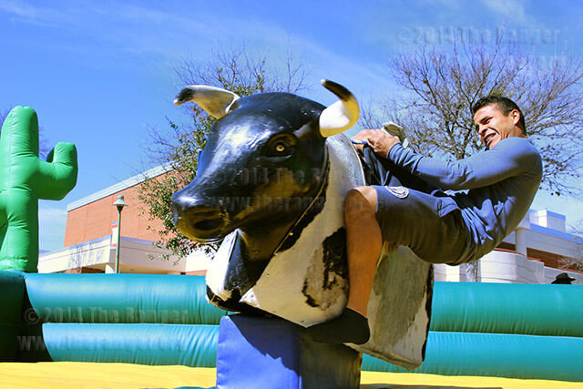 Architecture sophomore Jose Sierra fights being thrown from the mechanical bull at Rodeo Round-up Wednesday in the mall. The mechanical bull was rented by the office of student life for four hours at a cost of $1,150. Photo by Daniel Carde