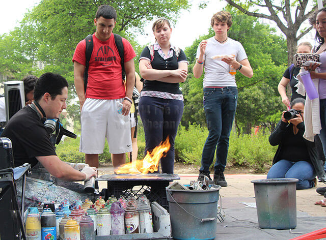 Carlos Flores, artist and senior specialist of student success, dries wet paint with fire Wednesday in the mall. Nursing freshman Lyserica Ortiz, at far right, paid $40 for a painting. Flores graduated from this college in 2005. Photo by Daniel Carde