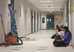 Nursing sophomore Kate Motsko studies adjacent to debris from a ceiling tile Feb. 17 from Room 353 of Chance. Repairing the roof is causing flame-retardant material applied to pipes to shake off and fall on ceiling tiles. The tiles then collapse under the weight. Photo by Carlos Ferrand