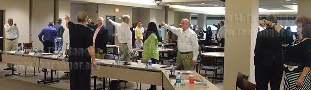 """Trustees and administrators of the Alamo Colleges point to where they think north is after spinning with their eyes closed at a board retreat Saturday in Sutton at St. Philip's. Different """"norths"""" were meant to represent different educational approaches. Photo by Siobhan O'Donnell"""