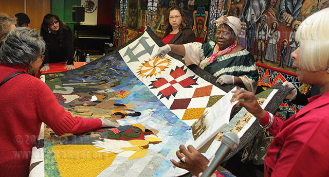 "Quilter Nina Fennel points out the different people represented on a quilt depicting the Underground Railroad during ""Piecing it All Together: Quilts and Their Role in Art and History,"" a panel during Black History Month Feb. 25 in the Fiesta Room of Loftin. On the far side of the quilt, Harriet Tubman is carrying a gun because if someone tried to turn around and go back, she would kill them, Fennel said. Fennel worked with other quilters for two years hand-quilting the people and piecing together the bordering blocks. ""This is our idea of how they might have dressed and what they might have looked like,"" she said.  Photo by Mandy Derfler"