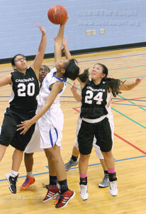Despite being double-teamed, business sophomore Toni Barnes is able to get above Lady Cardinal guards Yessenia Velazquez and Alana Valdez, and score 2 points Wednesday in St. Philip's 66-47 loss against the University of Incarnate Word in the health and fitness center. Barnes scored 14 points in the game. Photo by Carlos Ferrand