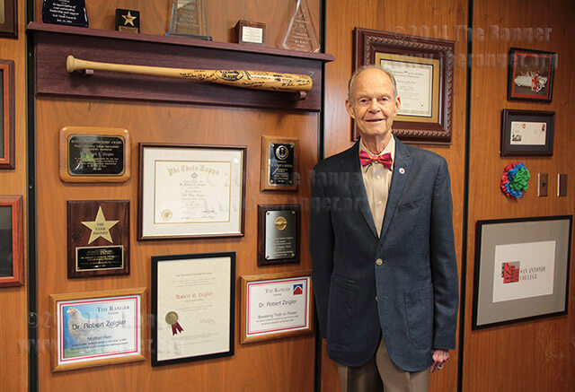 President Robert Zeigler poses with a few of his awards in his office April 22. File