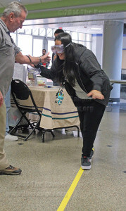 "Officer Charlie McLennen with the ACCD crime prevention unit assists nursing sophomore Gianina Ledesme as she attempts to maintain her balance using simulator goggles. The goggles are part of an Alcohol and Drug Awareness event today in Loftin to inform students of the effects of drunk driving. Ledesme said she ""definitely will not try drinking and driving."" Photo by Melissa Perreault"