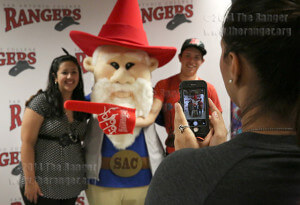 Nursing sophomore Shirley Ramierz takes a picture Thursday of nursing freshman Ashley Kaples and engineering freshman Edwin Velazquez with Gnome Ranger in the Fiesta Room of Loftin. The spirit figure took pictures with students to celebrate his first birthday. Photo by Daniel Carde