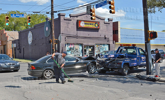 Robert Hillburn of Texas Towing sweeps up debris to tow Clint Babcock's car today at West Dewey and Main while Babcock looks on. Babcock's car collided with a green Montero Sport Monday. Photo by Neven Jones