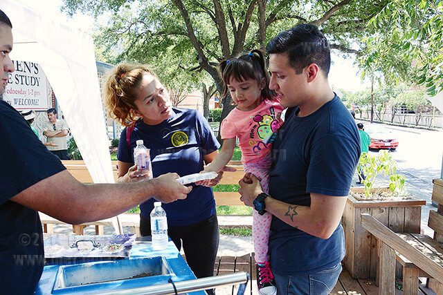 Nursing sophomore Ana Chavez and husband, Alfonso Chavez, take their daughter Scarlett, 3, to get a paleta at the Christian Student Center, 301 W. Dewey. The center handed out free sausage wraps, paletas and cold water Monday at 11:30 a.m. The center staff will hand out more free food Tuesday until they run out. Photo by Neven Jones