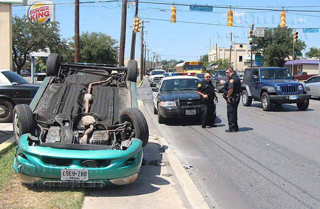 Officers Mike Lopez and Amador discuss a flipped car while traffic is directed around an accident site Monday at San Pedro and Laurel. Another driver swerved into the Kia Rio trying to avoid a stopped pickup. Photo by Mandy Derfler