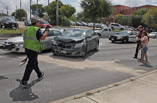 Tow truck operator Mike Medrano shovels broken debris while nursing freshman James Laform and wife Rosalinda Claudio take photos of the accident and 2009 Toyota Corolla Wednesday at San Pedro and West Courtland. Photo by Adriana Ruiz