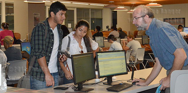 Chemistry sophomore Ernesto Alva and engineering sophomore Natalya Casas ask Librarian Tom Bahlinger about reserving a study room Monday on the second floor of Moody. When Bahlinger started working at the library 15 years ago, there were 11 full-time librarians on staff. By Jan. 9, the full-time staff will be cut to five.  Neven Jones