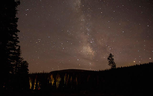A campfire, about three football fields away, lights pine trees beneath the Milky Way Sept. 20 at Mirror Lake, Utah. At an elevation of 10,050 feet in the Uinta Mountains about 75 miles east of Salt Lake City, in the Uinta-Wasatch-Cache National Forest, light pollution and other pollutants are minimal.  Courtesy Daniel Carde