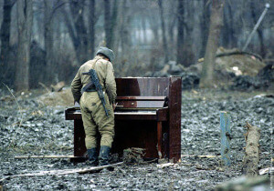 A Russian soldier inspects an abandoned piano in war-torn Chechnya in 1994.