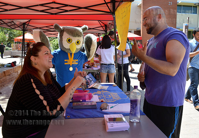 Business administration sophomore Ann Marie Heesbrook explains the benefits of being part of Phi Theta Kappa to kinesiology sophomore Federico Pizeno at the organization showcase Wednesday in the mall. Kim-Briana Lorine, Phi Theta Kappa president, dressed as the Beta Nu owl. The showcase promoted clubs and recruited new students.  Ayesa Hinojosa