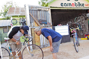 Navarro Academy graduate Clement Ronald inspects his bicycle's handlebar as nursing freshman Daniel Esquivel makes sure it is aligned with the head tube and fork below Sept. 2 during open shop night at EarnABike on 2619 Guadalupe St. San Antonio's premiere bicycle co-op helps participants build their own bicycle by using donated bicycle frames and parts.  Photo by Jennifer M. Ytuarte