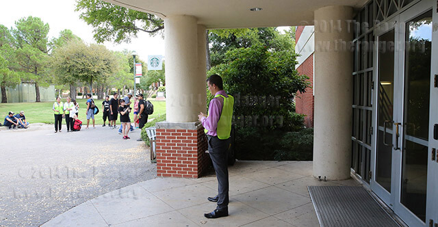 While blocking the north entrance of Loftin, Mark Bigelow, coordinator for student success in the office of student life, checks his Facebook after a fire alarm sounded around 1:50 p.m. today. Photo by Daniel Carde