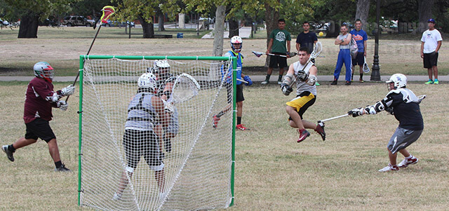 Civil engineering freshman Max Tesalona, who is not wearing a helmet, tries to score through fire science freshman and goalie Joshua Wells Saturday during a lacrosse scrimmage at San Pedro Springs Park.  Taylor Tribbey