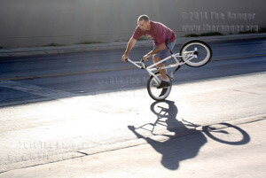 Bobby Burge, engineering alum of this college, practices tricks Saturday outside of Leather Hands BMX Bike School and Repair Shop, 222 Fredericksburg. Owner Paul Magallenez and Burge are bike enthusiasts and ride freesyle together. They have been freestyle riding for more than 20 years. Photo by Pam Paz