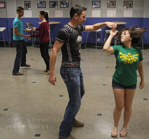 Psychology sophomore Jacob Wong guides math freshman Brianna Jimenez as she twirls while dancing the cha-cha Monday during salsa lessons in the Fiesta Room of Loftin. Jimenez said a friend made her dance, but she had fun.  Photo by David Guel