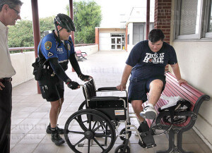 Alamo Colleges Officer Michael Castillo helps accounting freshman Robert Cottrell into a wheelchair after he tripped and rolled his ankle on uneven tiles on the balcony between Loftin and Gonzales at about 10:40 a.m today. Cottrell chose not to call EMS. To report any hazards, contact facilities at 210-486-1236.  Photo by E. David Guel