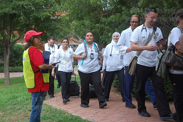 Karen Gonzalez, academic lab technician for allied health, directs nursing students Oct. 2 from the nursing complex into Chance for a hail storm portion of a fire drill. Photo by Ian Coleman