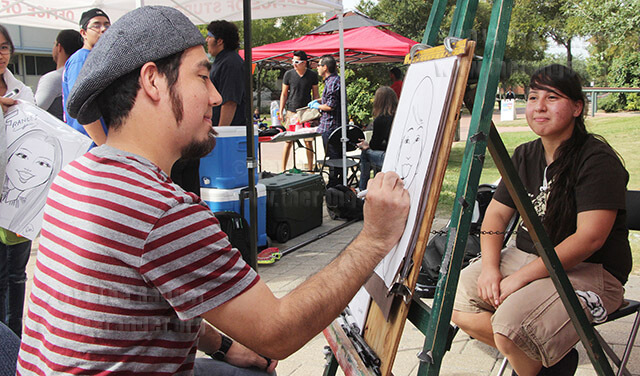 Freelance caricature artist Randon Martinez draws a portrait of liberal arts sophomre Dawin Vega during Octoberfest Wednesday in the mall. The booth sponsored by student life provided caricatures at no charge.  Photo by E. David Guel
