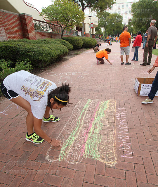 A student draws with chalk on the walkway between Loftin and Chemistry and Geology Oct. 2013 at The Ranger's Chalk Day event to celebrate free speech. The Ranger will be hosting their next Chalk Day event at 10 a.m.-noon Oct. 6 in the mall walkway. File Photo