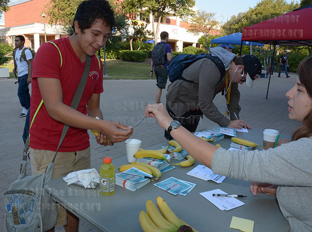 Liberal arts freshman Luis Mares takes a nonpartisan voter guide from MOVE San Antonio's Bela Kriger today in the mall. MOVE San Antonio will return 8 -11 a.m. Wednesday. Early voting began today and will continue through Oct. 31. Photo by Neven Jones