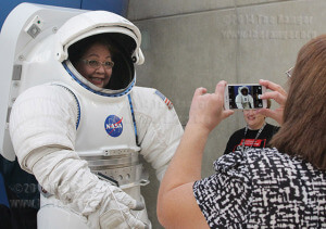 Rose Gonzales and Janet Lozano, administrative assistants, take pictures with a replica NASA space suit during the VIP grand opening of Scobee Education Center Friday.  Photo by E. David Guel