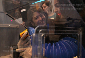 Fifth grader Sofia Lynton, 10, illuminates the teeth of classmate Shaelyn Marks, 10, using a temperature reader gun with her hand in a glove box in the space station during the VIP grand opening of Scobee Education Center Friday. Students from Scobee Elementary were selected for a field trip to the center.  Photo by E. David Guel