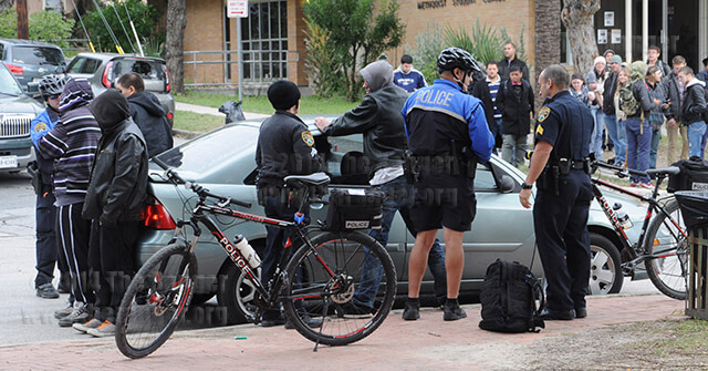 "Campus police confront four suspects Nov. 12 at the corner of Belknap and Dewey. Only one suspect — in the black hoodie at left — was taken into custody under investigation of criminal activity and a Bexar County warrant. Officers are Patrolman Michael Long (far left), Cpl. Shyla York, Patrolman Miguel ""Michael"" Castillo and Sgt. Guillermo Perez.  Photo by sIan Coleman"