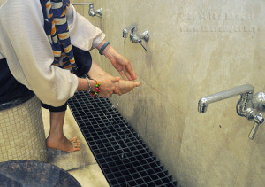 "Martinez demonstrates wudu, or washing before prayer. Muslims recite ""bismillahi al r-rahmani al r-rahim,"" then wash their hands, mouth, nose and face three times. Wash the right arm to the elbow first then left, put water on the head front to back, clean behind the ears with thumb. Finally the feet are washed between the toes starting with the right foot.  Photo by Neven Jones"