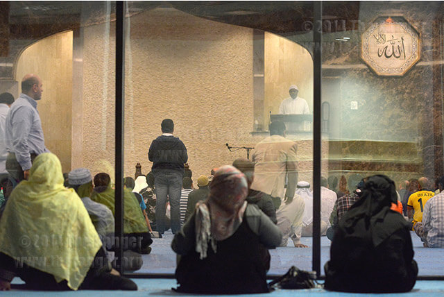 A group of women look through the glass separating the men's side of the mosque from the women's as the imam speaks before Friday group prayer.  Photo by Neven Jones