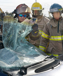 First Responders Academy instructor and Bexar-Bulverde Fire Department volunteer Cheryl McCall demonstrates how to safely pull a broken windshield off a car Oct. 31 at Texas Auto Salvage as fire science students Darius Hart and Ricky Huizar watch.  Photo by Neven Jones