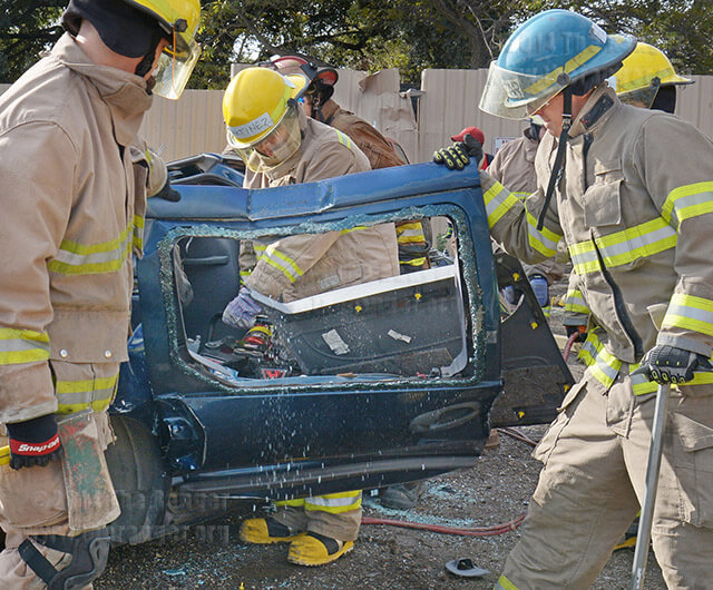 Jimmy Martinez cuts a car door using the Jaws of Life while classmates Matthew Klavon and Ricky Huizar hold it open.   Photo by Neven Jones