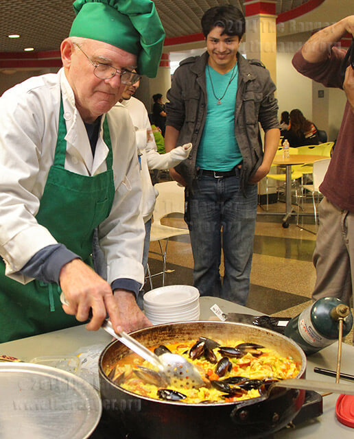 Robert Kniseley, Spanish adjunct and chef, prepares paella as psychology sophomore Mikael Moreno watches Nov. 19 in the cafeteria of Loftin. Paella is a dish that dates back 400 years and originally included rabbit.  Photo by Milena Arias