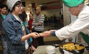 Mathew Ramirez, computer information systems freshman, accepts a plate of paella from Robert Kniseley, Spanish adjunct and chef, Nov. 19 in the cafeteria of Loftin. Kniseley prepared the traditional Spanish dish for International Education Week.  Photo by Milena Arias