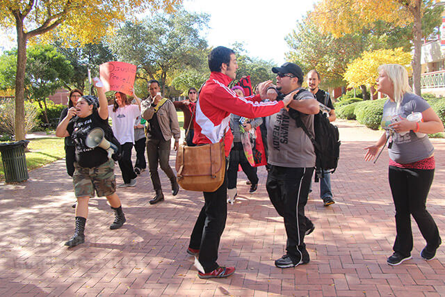 Education sophomore Ricardo Henriquez grabs the arms of paramedic sophomore Chris Woollen today in the mall area during a protest about yesterday's grand jury verdict to not indict Ferguson, Mo., police officer Darren Wilson in the shooting death of Michael Brown. Henriquez is against the grand jury's ruling and ripped Woollen's sign that supported Wilson.  Photo by Christopher A. Hernandez