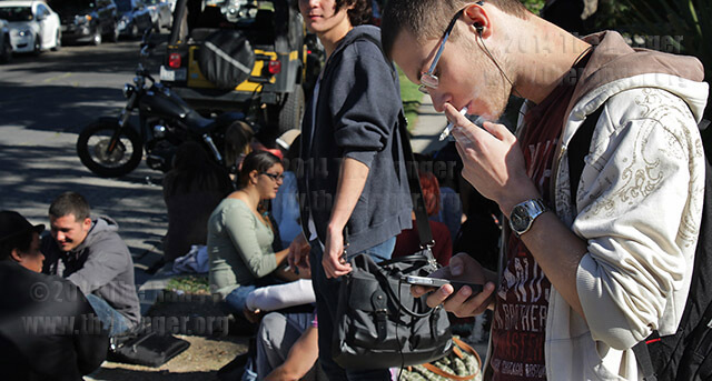 """Liberal arts freshman Arthur Chibisov smokes a cigarette and checks his phone Oct. 15 at Dewey and Belknap. Chibisov, an international student, said """"In Latvia, you can smoke everywhere, but here it's unusual.""""  Photo by E. David Guel"""