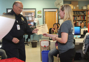 "Deputy Chief Joe Pabon receives the ""Sure Thing"" award from news editor Maura Callahan during Source Awards Nov. 19 in The Ranger newsroom in Loftin. His award notes him as The Ranger's most reliable source this semester.  Photo by Milena Arias."